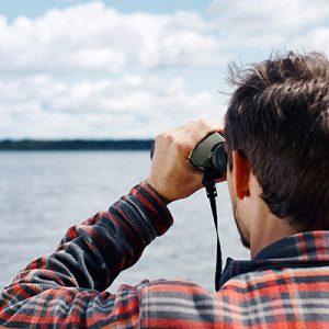 Close up back portrait man looks across a lake through binoculars
